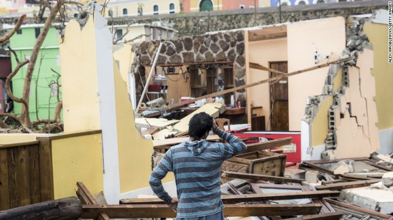A photo by CNN of a resident in San Juan, Puerto Rico, looking at the damage to his house.